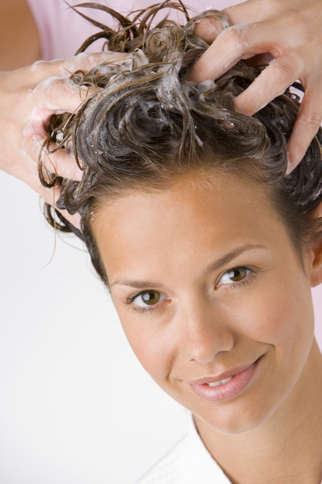 Hands washing woman's hair