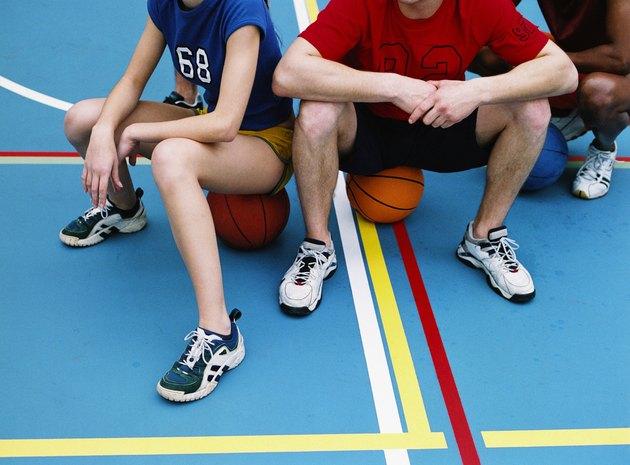Close-up of three basketball players sitting on basketballs