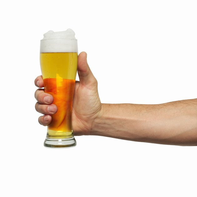 Close-up of man's hand holding glass of beer