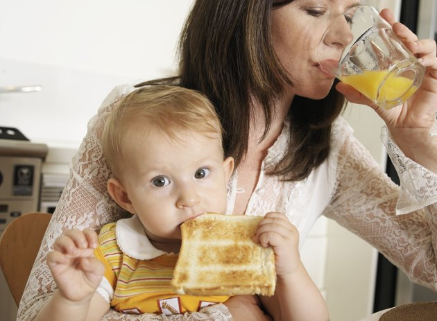 """""""Mother sitting with daughter (9-12 months) on laps, having breakfast"""""""