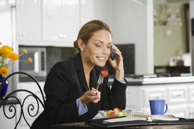 Hispanic businesswoman eating breakfast