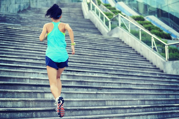 young sports woman running up on stone stairs