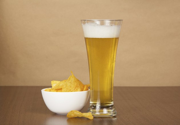 Glass of cold beer and chips on the plate