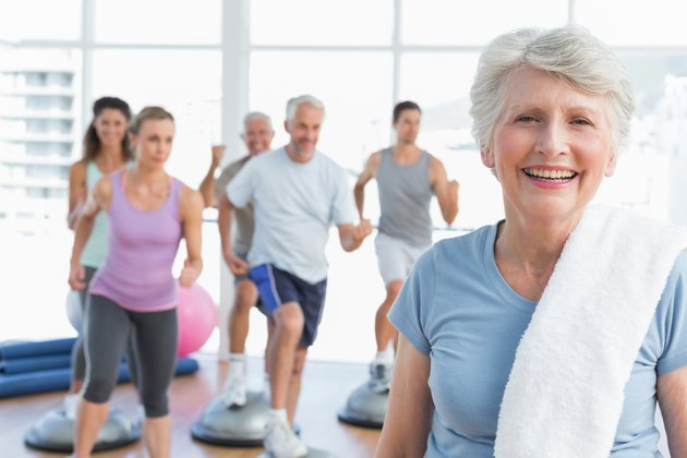 Senior woman with people exercising in fitness studio