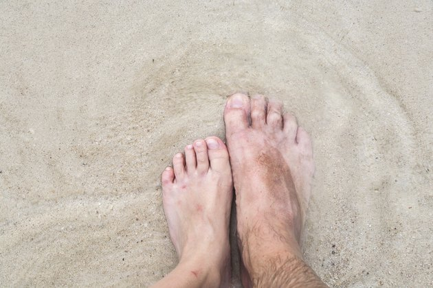 feet of father and son at the beach