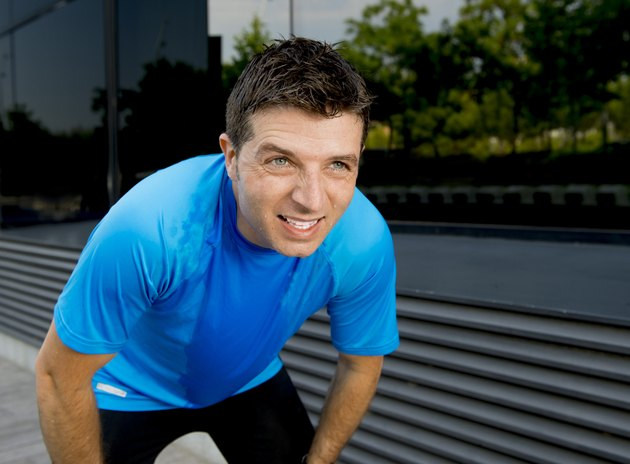 young attractive man leaning exhausted after running session sweating