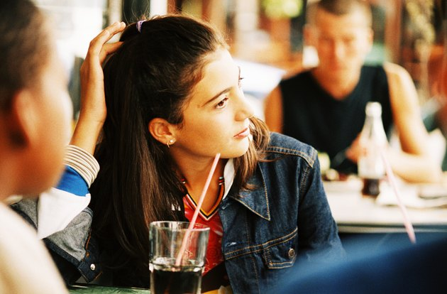 Teenage girl (14-16) sitting in a cafe with other people in the background
