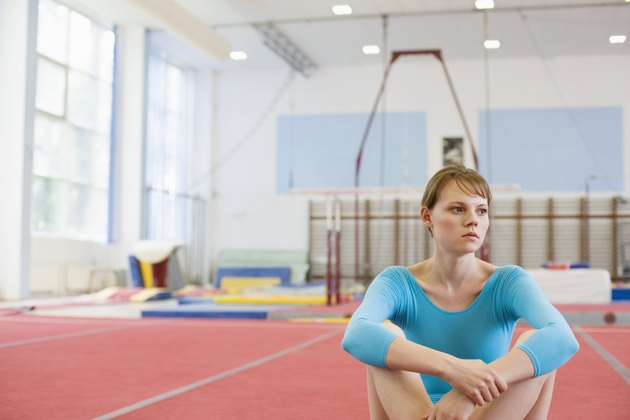 Serious young gymnast sitting on gym mat