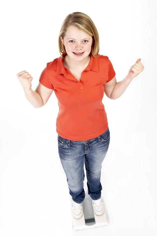 Teenage girl on weight scale
