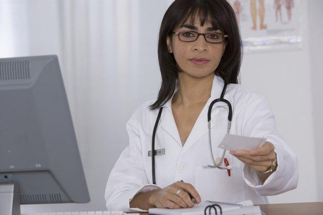 Female doctor handing over prescription