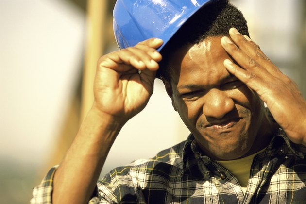 Close-up of a construction worker touching his head and removing his hardhat