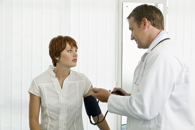 Doctor examining blood pressure of patient
