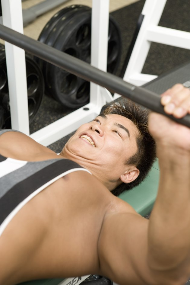 Man lifting barbell in gym, high angle view, differential focus