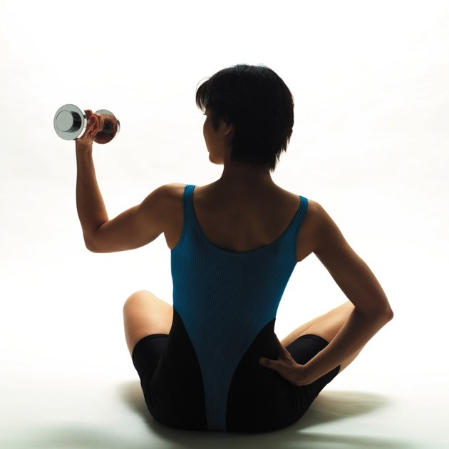 A woman in Leotard exercising with a dumbbell, Rear View, Silhouette