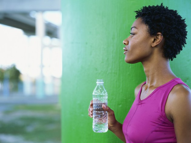 Side profile of a young woman holding a bottle of water