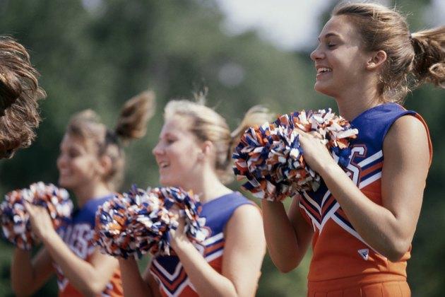 Side profile of three cheerleaders holding pom-poms
