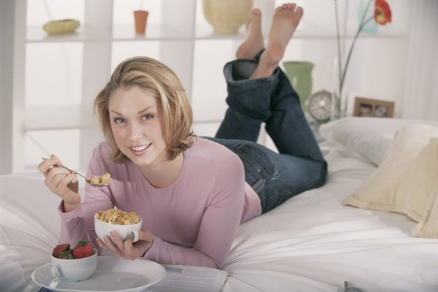 Portrait of woman eating breakfast in bed