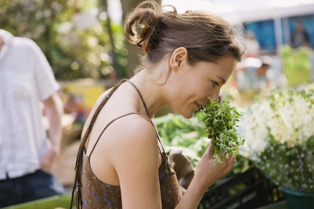 Woman smelling herbs at outdoor market