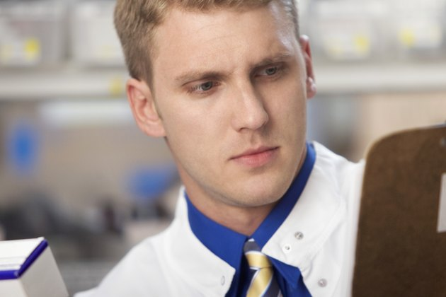 Close-up of a male pharmacist looking for prescription in a medical store