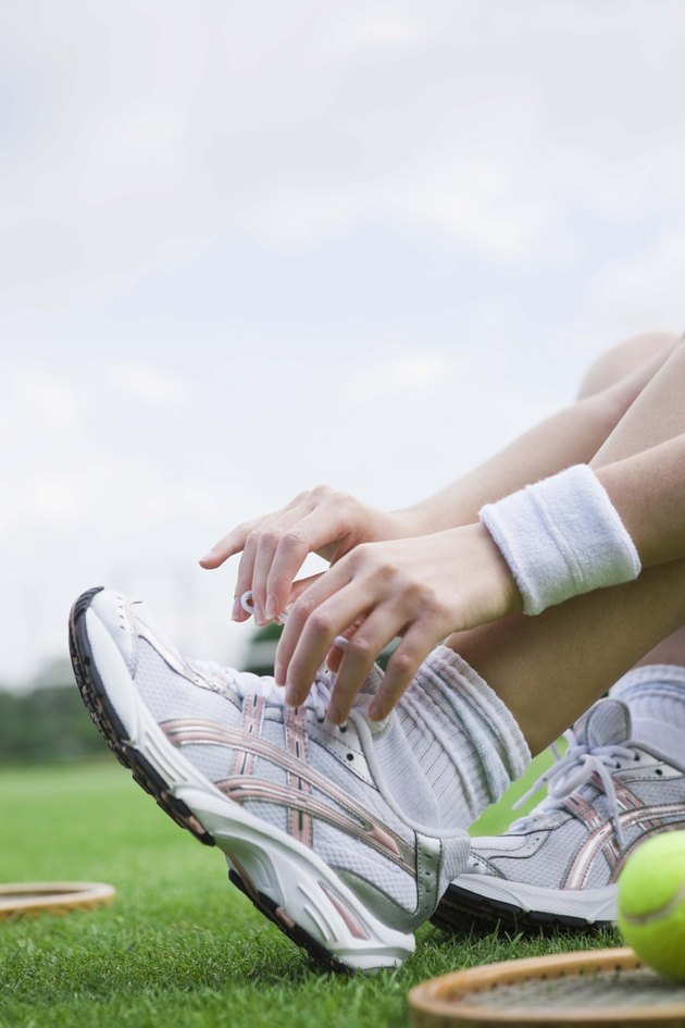 Woman tying shoelaces on tennis court
