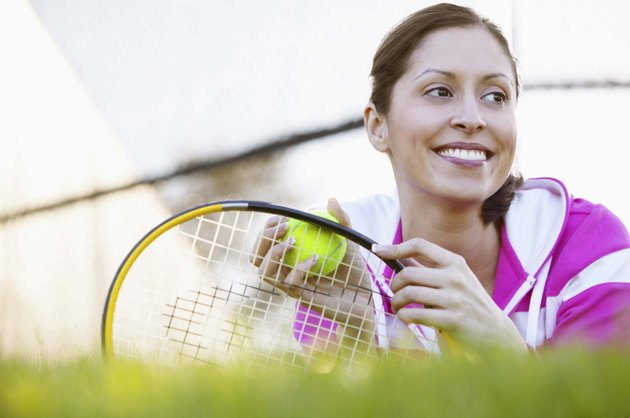 Woman with tennis equipment on grass