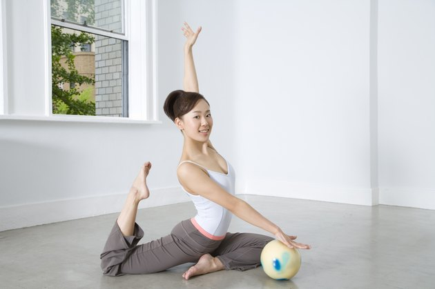 Portrait of a woman practicing rhythmic gymnast performing with ball