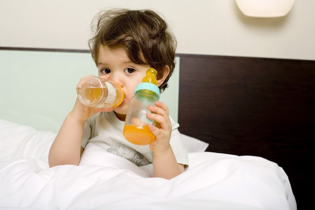 Child drinking juice in bed
