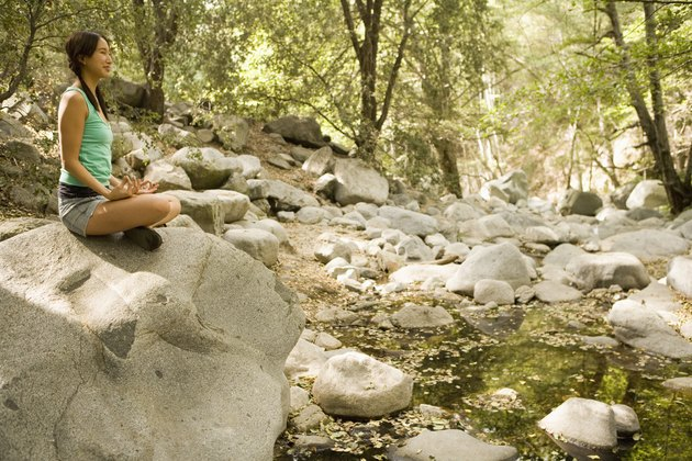 Woman seated on rock meditating