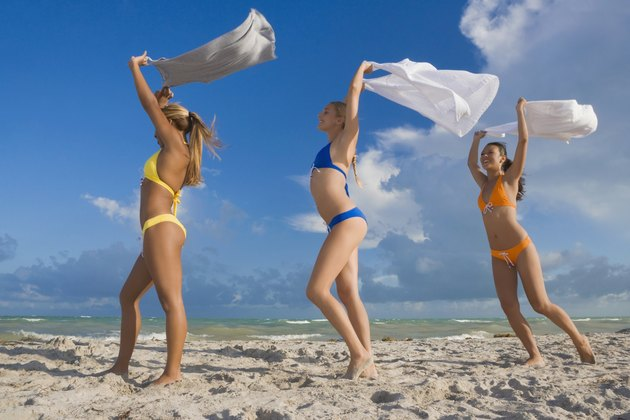 Hispanic women in bikinis holding skirts in wind