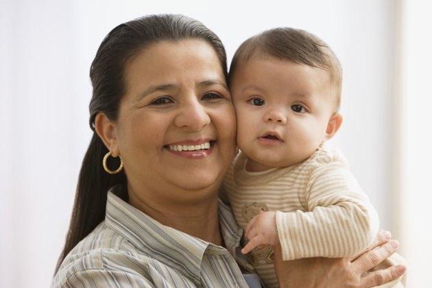 Hispanic mother hugging baby