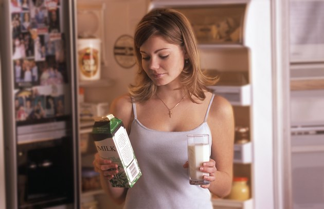 Girl getting glass of milk from fridge