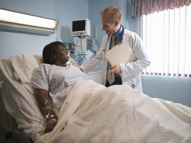 Male doctor talking to female patient lying in hospital bed