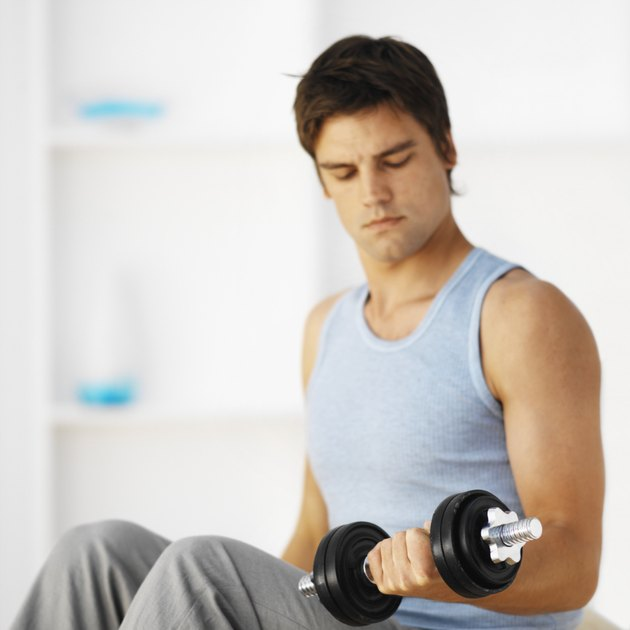 Close-up of young man lifting dumbbell