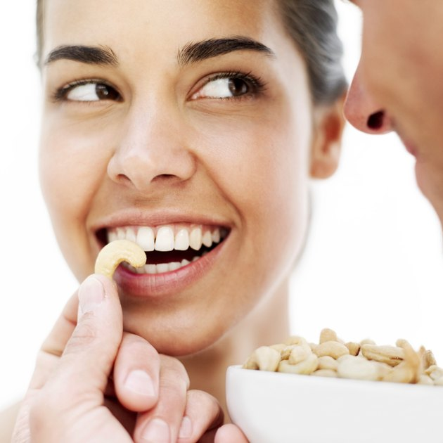 young man feeding a young woman cashew nuts