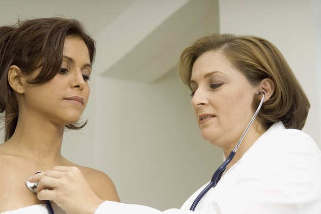 Female doctor examining a mid adult woman with a stethoscope