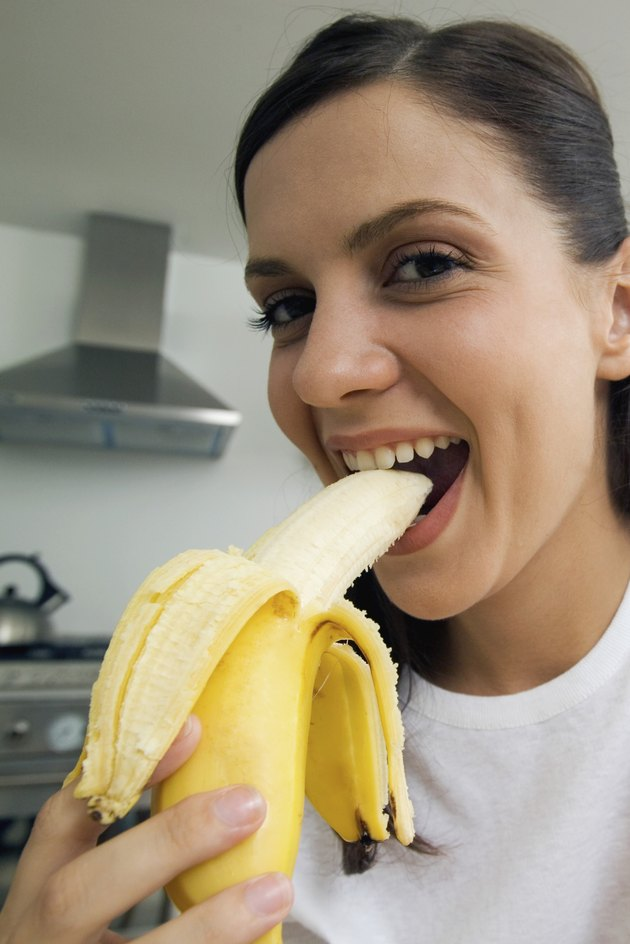 Close-up of young woman eating banana, low angle view, selective focus