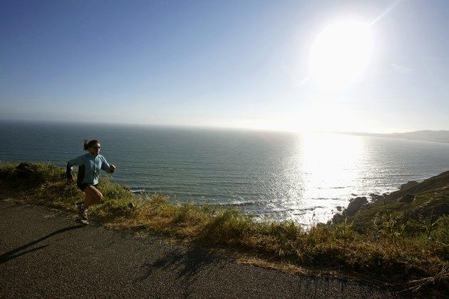Woman jogging on road beside ocean,  California,  USA