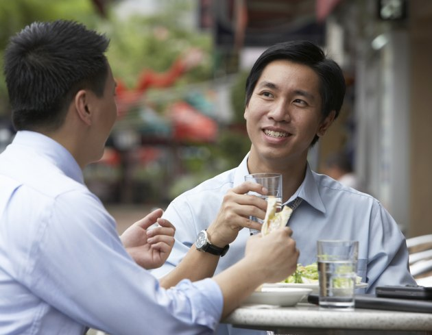 Two businessmen having lunch at outdoors cafe