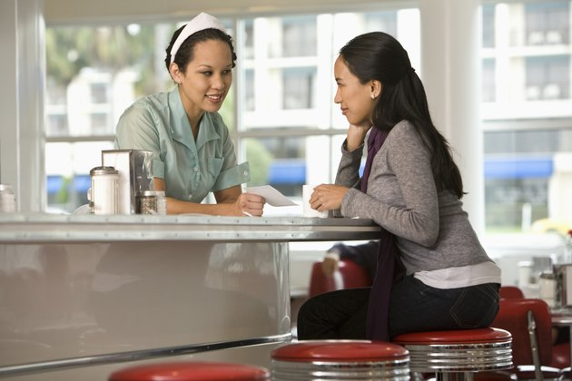 Asian waitress giving bill to customer