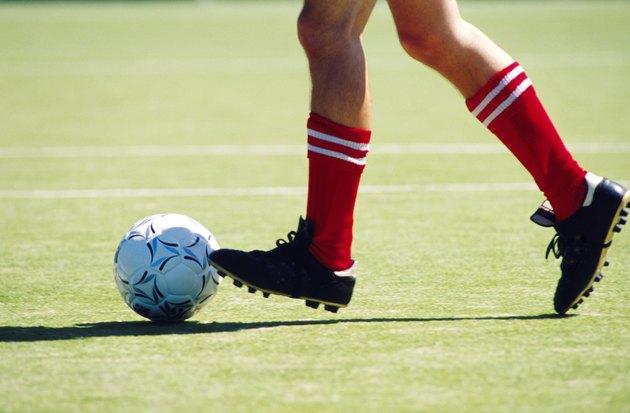 Feet of soccer player kicking ball