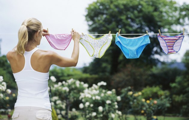 Rear view of a young woman hanging undergarments on a clothesline