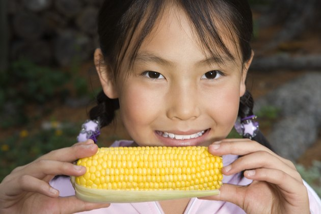 Girl holding ear of corn