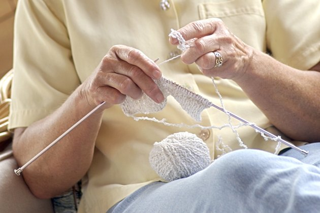 Close-up of a mature woman's hands as she crochets with white yarn.