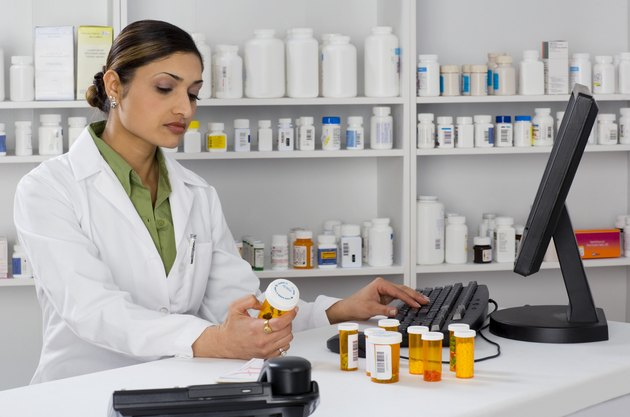 Pharmacist looking at pill bottle and using computer