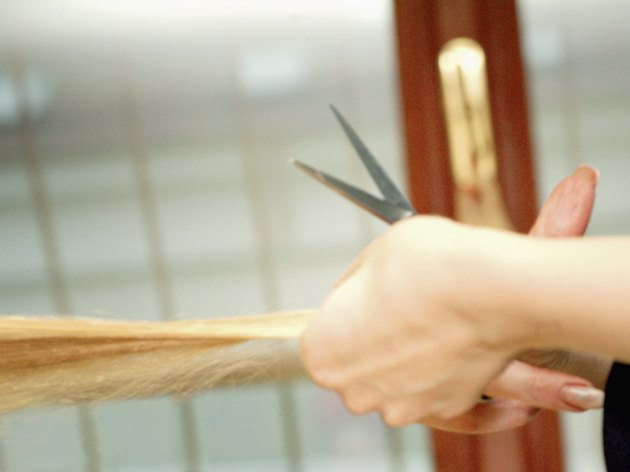 Close-up of a hairdresser's hand cutting a woman's hair with scissors