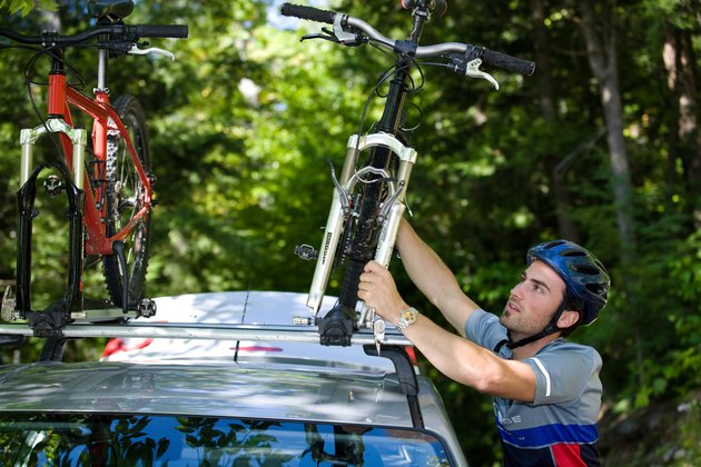 Man fastening bikes on car rack