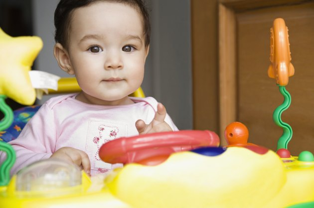 Hispanic baby girl playing with toy