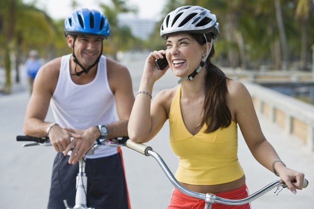 Hispanic woman on bicycle talking on cell phone while boyfriend waits