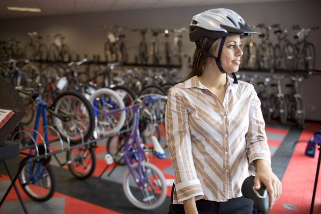 Woman in safety helmet in bike shop