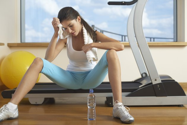 Woman sitting on treadmill after work out in gym